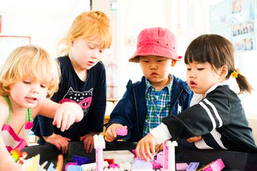 A group of children play together with bricks.