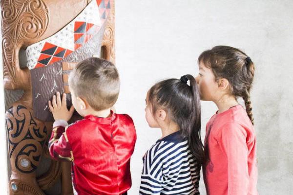 Three tamariki looking at a carving.