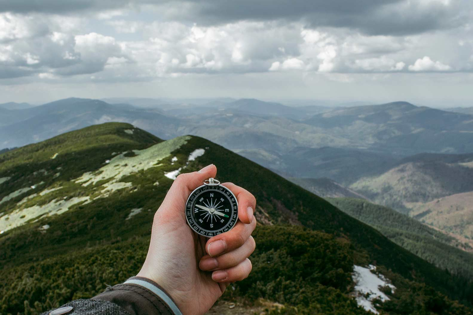 Hand holding a compass over a mountainous landscape.