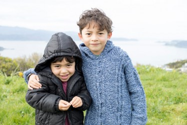 A tamariki with their older brother standing beside them with their arm around them.