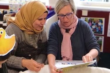 A former refugee works alongside a kaiako.