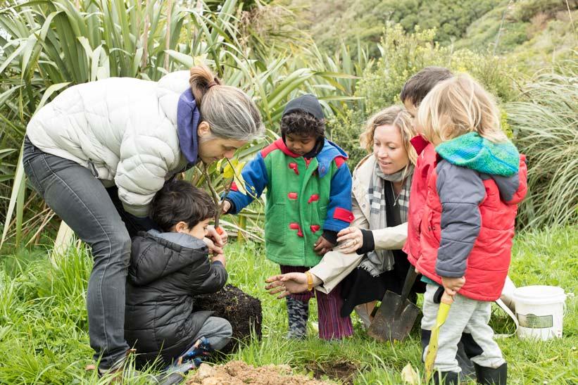 A kaiako, whānau and tamariki plant a seedling together.