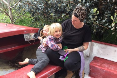 A parent with two children playing on a car at playcentre.