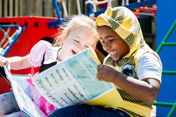 two tamariki enjoying looking at their learning stories together.