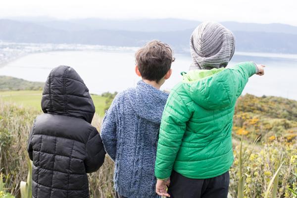 Three tamariki overlooking a bay and pointing.