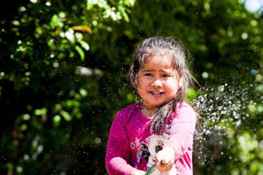 Tamariki playing with a hose outdoors.