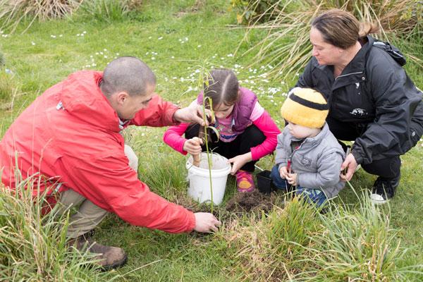 Kaiako, tamariki, and a parent planting a tree together.