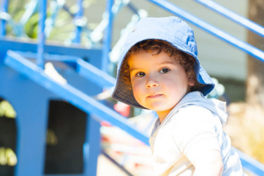 Toddler standing by play equipment