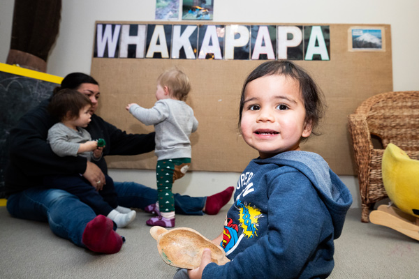 Tamariki smilling with a kaiako sitting with other tamariki in the background and a sign with whakapapa on it.