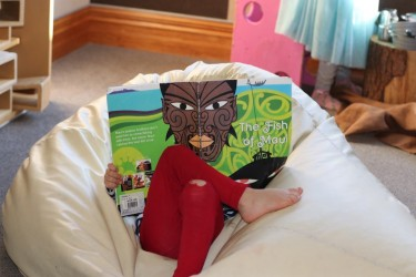 Child reading book about Maui.