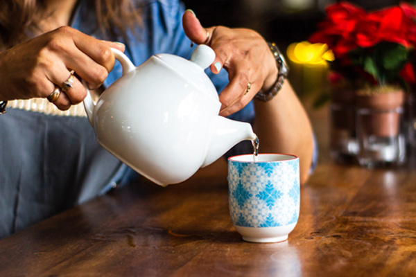 Woman pouring a cup of tea.