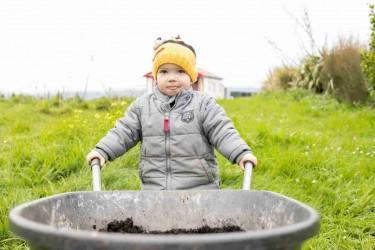 Child with a wheelbarrow.