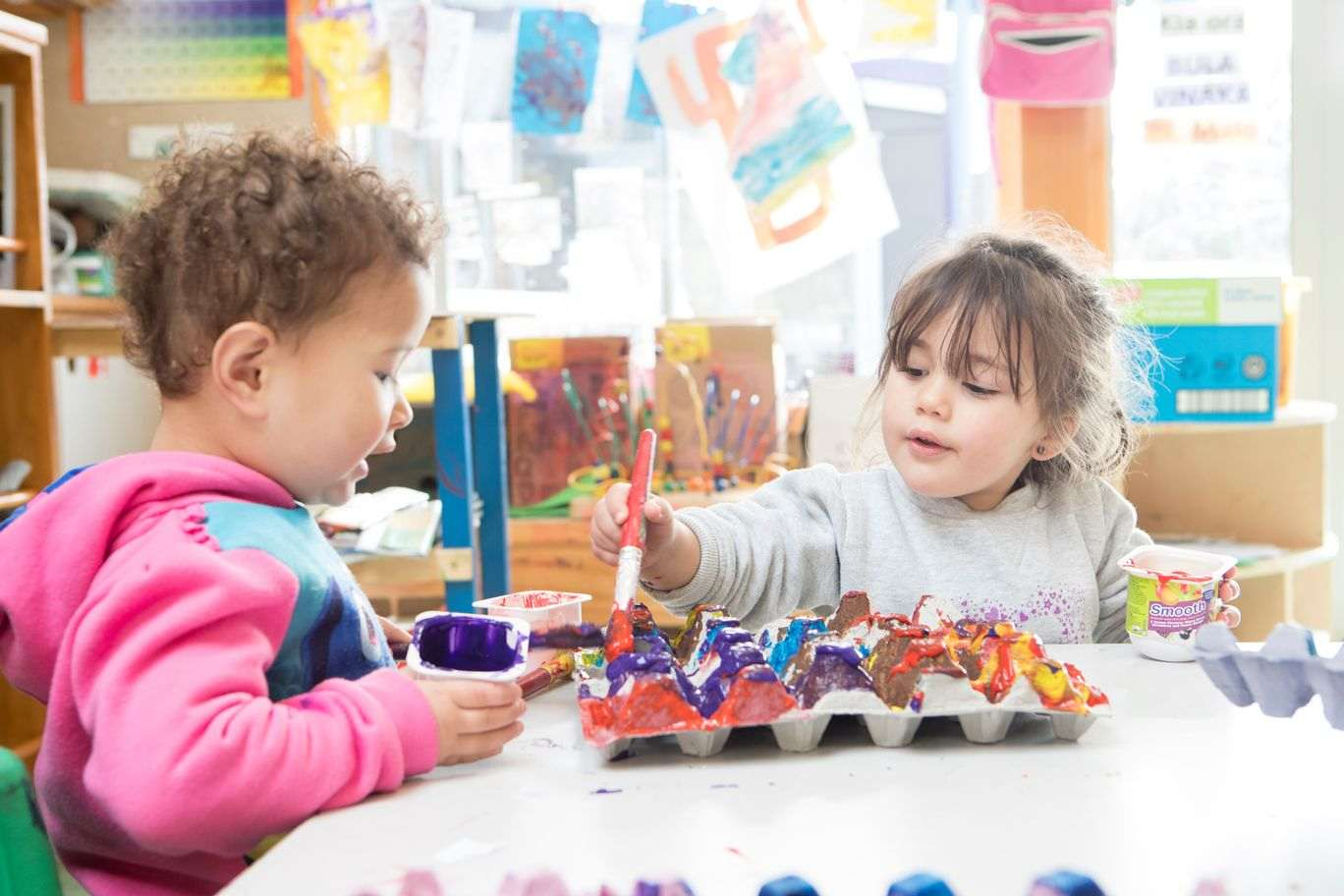 Two children painting an egg box.