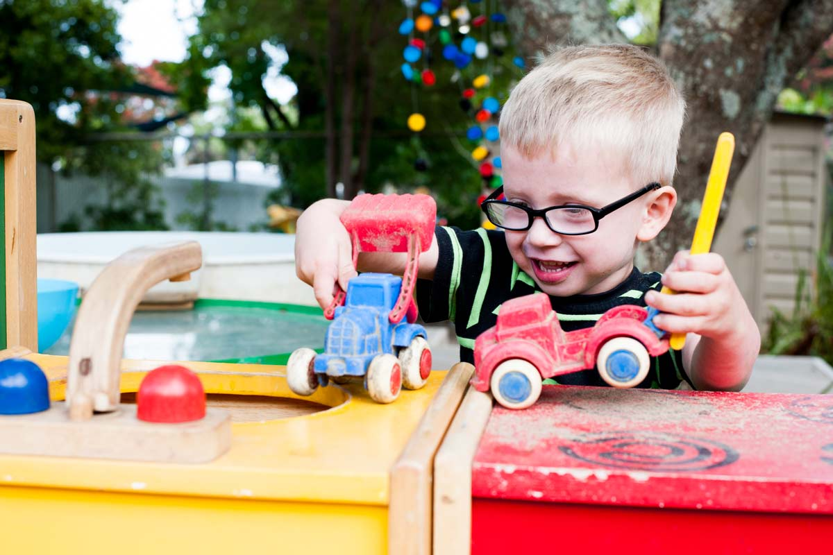 A child happily playing with some vehicles.