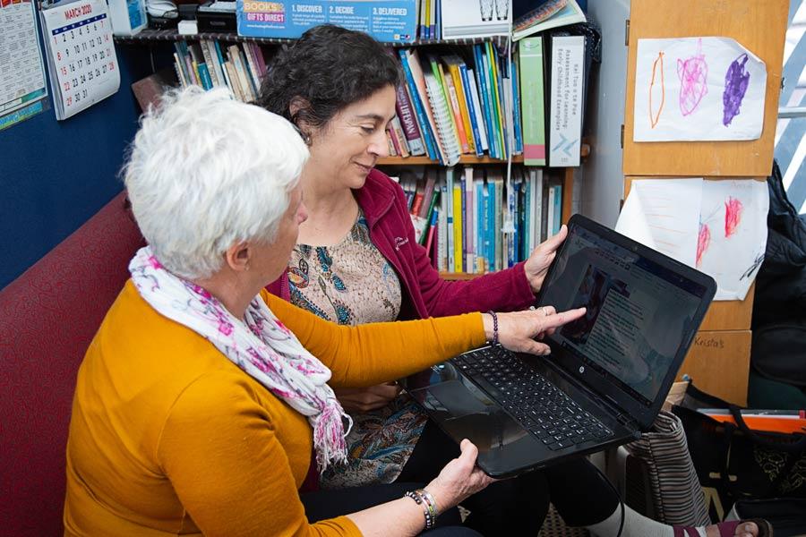 Two kaiako discuss data on a laptop computer.