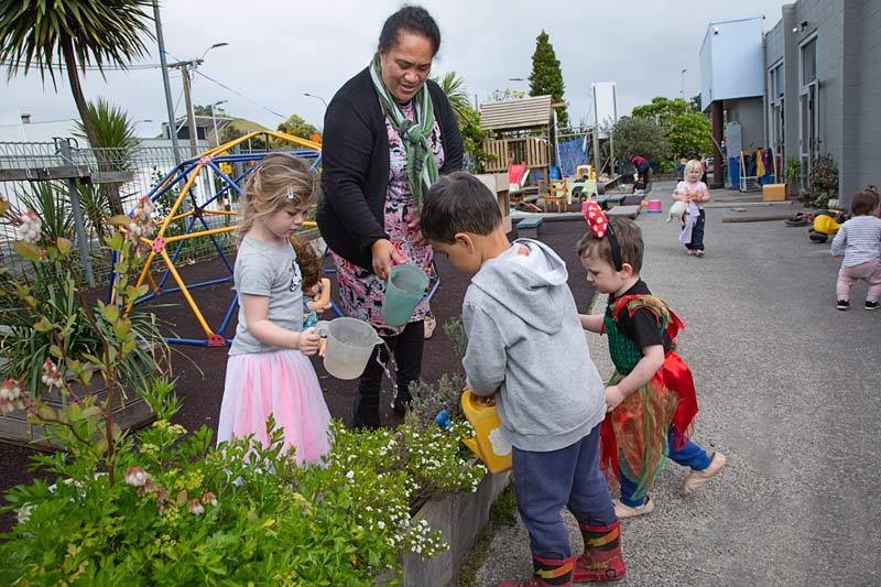 A kaiako and a group of children talk together while watering the garden.