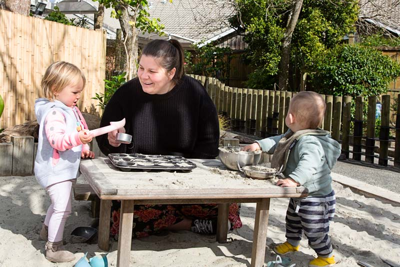 A kaiako talks with two tamariki while playing with bowls and sand.