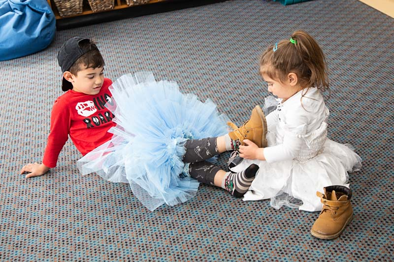 One tamariki helps another with taking off shoes