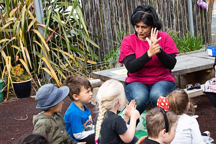 Kaiako signing waiata, Mā is white with a group of tamariki.