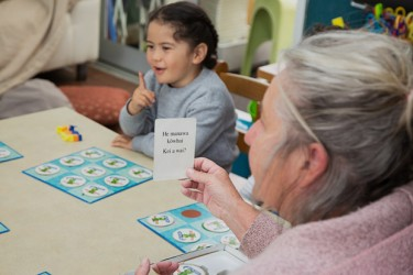 Kaiako and child playing a game to expand te reo Māori vocabulary.
