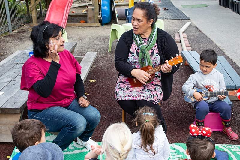 Kaiako sing, sign, and play the waiata Te aroha with a group of children