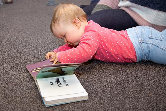 A kaiako and infant reading a book in te reo Māori.