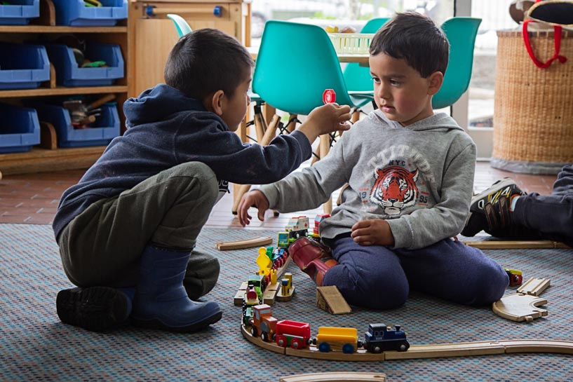 Two tamariki talking together over building a train track.