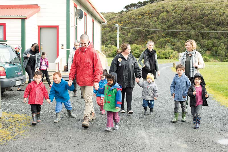 Whānau and kaiako walking together with a group of children.