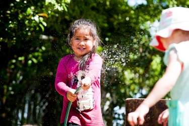 Child watering plants with a hose.
